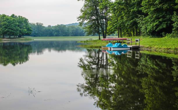 Soleado día de verano en el lago con botes de remo y canoas en el parque estatal Ohio Scioto Trail - foto de stock