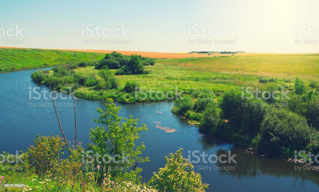 Sunny summer landscape with river,green hills,meadows and pastures. stock photo