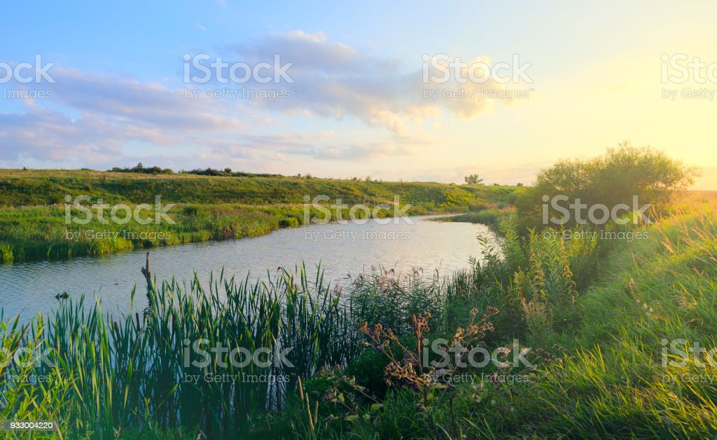 Sunny summer landscape.Green hills,fields and meadows.Sunset.Quiet stream.Calm.Warm sunlight.Beautiful clouds in bright blue sky. stock photo