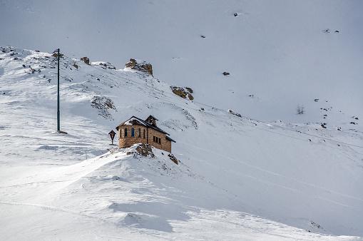 Sunny view of stone chapel in Dolomite Alps near Canazei of Val di Fassa, Trentino-Alto-Adige region, Italy.
