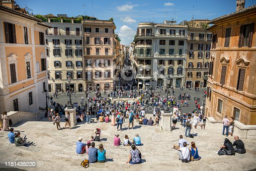 Rome, Italy, May 23 - A sunny view of Piazza di Spagna from the top of the stairway of Trinità dei Monti, a place visited by millions of tourists every year. This famous stairway was built in 1726 to a design by the Roman architect Francesco De Sanctis. At the center of the photograph is the Barcaccia, a 17th century Baroque fountain famous for its boat shape. Still in the center, it flows into Via dei Condotti, a very famous street for the shopping in the luxury shops of the most important Italian fashion brands.