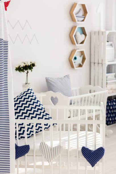 sunny wake-up in a cosy baby bed - marineblau schlafzimmer stock-fotos und bilder