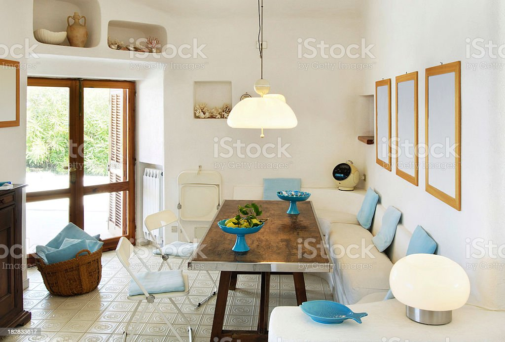 Sunny white living-room in beautiful seaside house with glass door stock photo