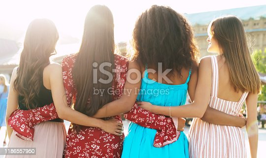 A group of four best friends in magnificent summer outfits are hugging each other and posing with their backs to the camera.