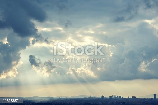 Cityscape with thick clouds and sunbeams shining through.