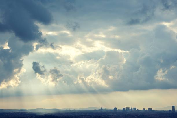 Sunrays coming through the clouds to brighten the city stock photo