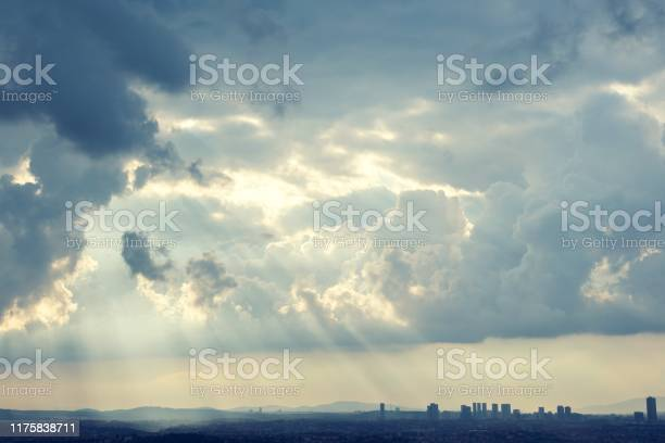 Photo of Sunrays coming through the clouds to brighten the city