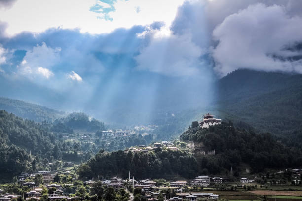 Sunrays leaking from  clouds over peaceful village in Bumthang valley, Bhutan. stock photo