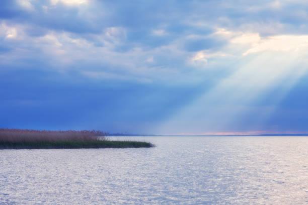 Sunrays shining through dramatic cloudy sky falling over a small island on lake Balaton in Hungary stock photo