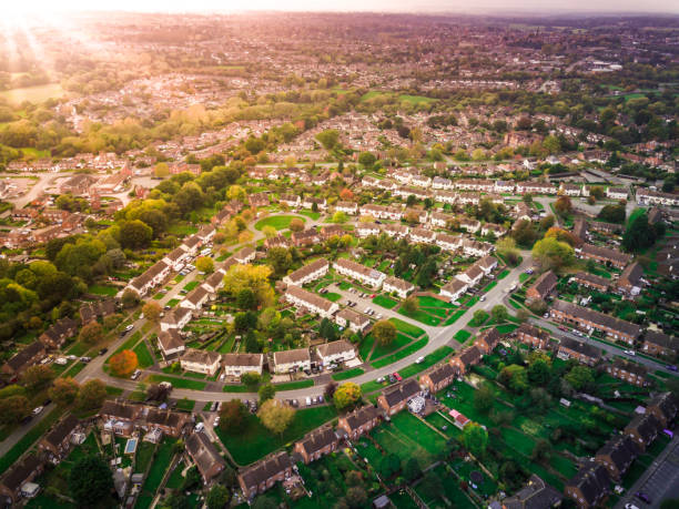 Sunrise above a British housing estate with fields and hills in the background. stock photo