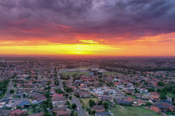 Sunrise above a residential suburbs  with streets, homes parks in the background. Dramatic lighting and warm colours give a homely effect. stock photo