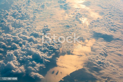540203788 istock photo Sunrise above clouds and sea from airplane window. Natural background. 1221861699
