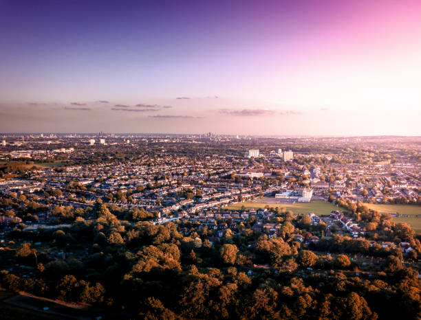Sunrise aerial view of London City Skyline and famous skyscrapers in the the background above a London housing estate. stock photo