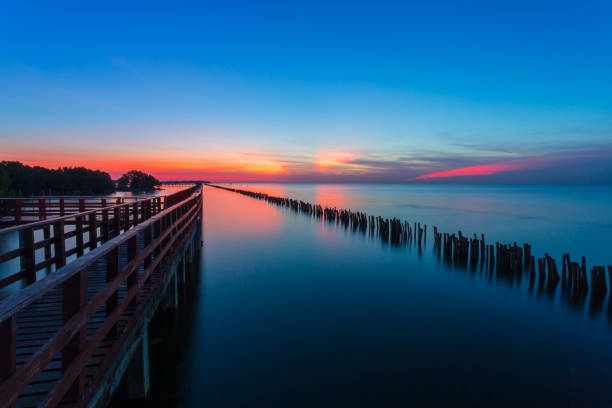 Sunrise and beautiful sky background at wooden red bridge over the sea at Gulf of Thailand, near by Tha Chin estuary, Samutsakhon province, Thailand stock photo