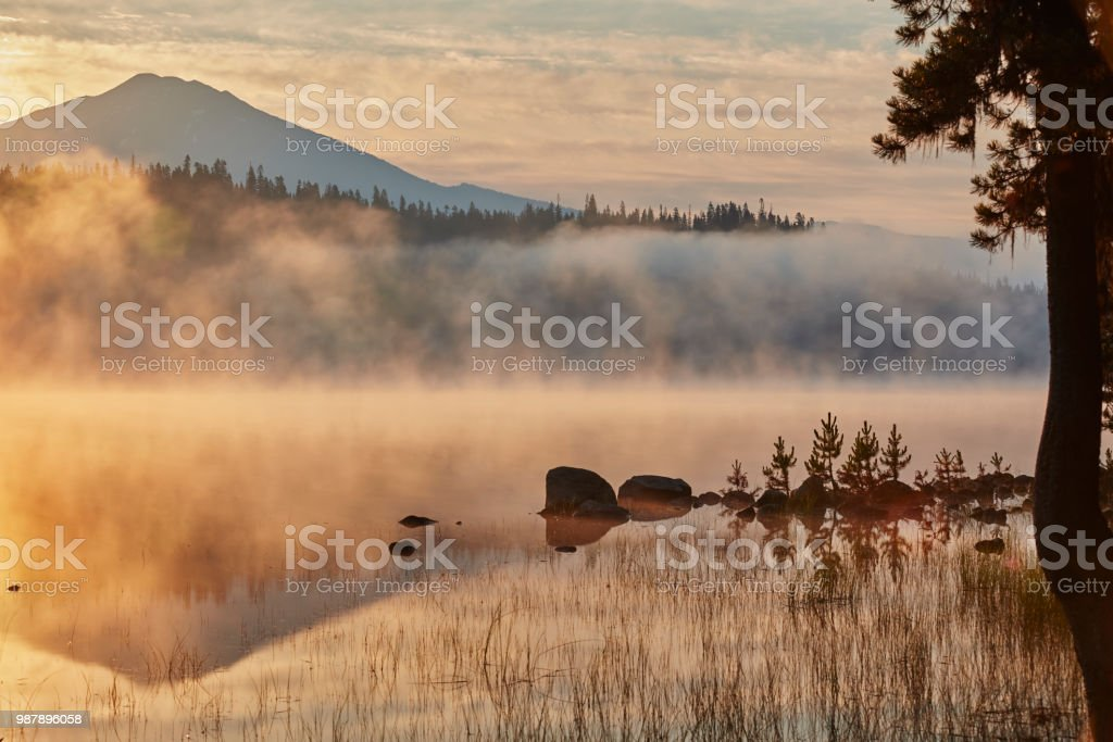 Sunrise and light fog rising off of Elk Lake in the Deschutes National Forest in the summer stock photo