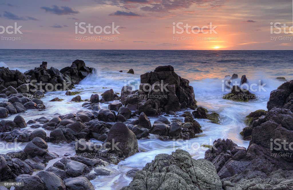 Sunrise and Minamurra volcanic rocks at low tide stock photo