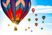 Many hot air balloons take flight at sunrise.