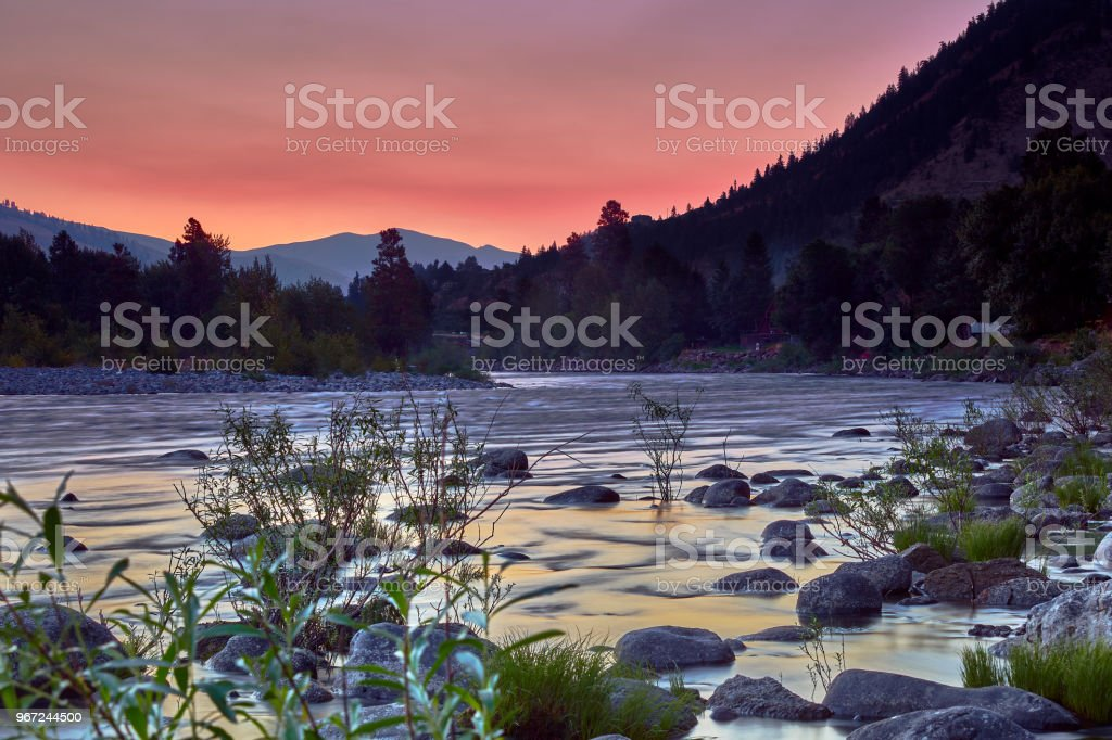 Sunrise at a bend in the Wenatchee River during fire season with an orange sky in the summer stock photo