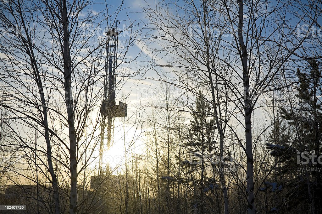 Sunrise at Drilling Rig through Trees royalty-free stock photo