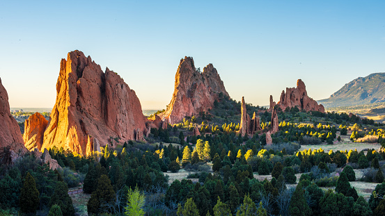 Sunlight peaks through the Garden of the Gods in Colorado Springs at sunrise.