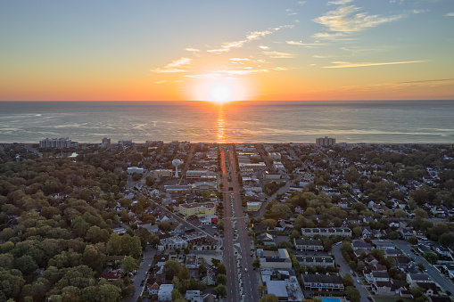 Photo shows sunrise at Rehoboth Beach where the sun is brighting the town. Photo was taken with a drone during summer and the sky is colorful.