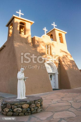 The first rays of sunlight on the bell towers of historic San Francisco de Assisi church in Taos, New Mexico. This Spanish mission was made famous in photographs by Ansel Adams.