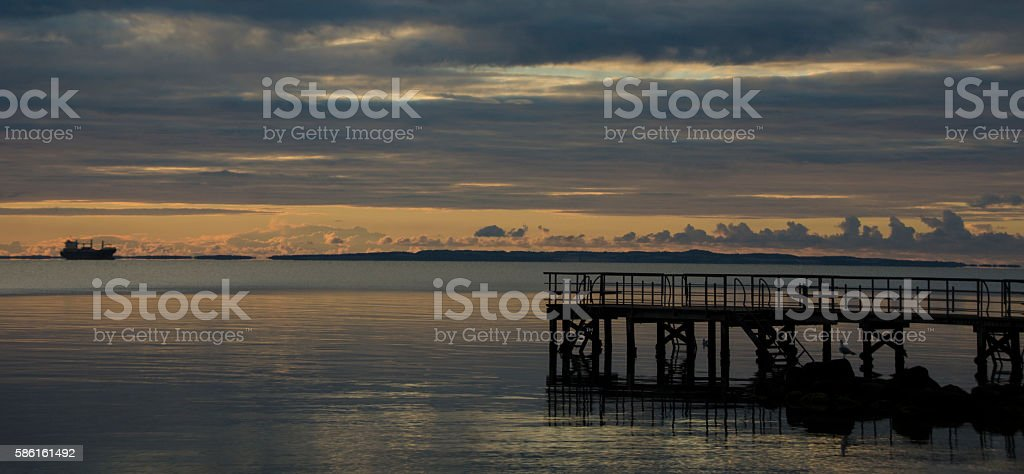 Sunrise at Sea with a bridge in the horisont stock photo