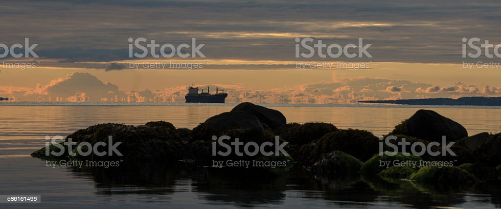 Sunrise at Sea with stones in front in the horisont stock photo