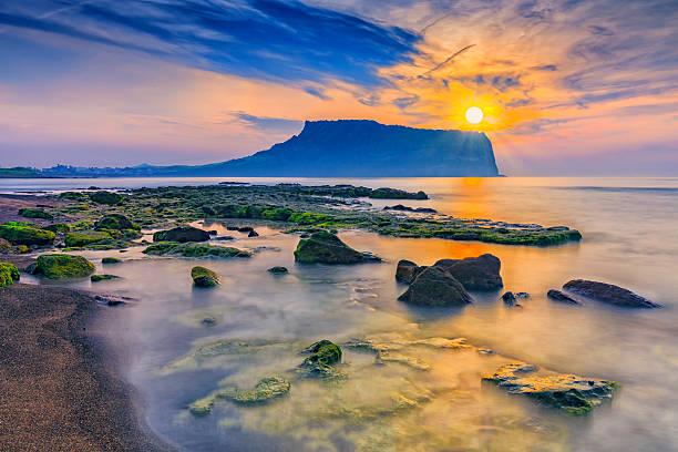 sunrise at seongsan ilchulbong, jeju island, south korea. - jeju island stock photos and pictures
