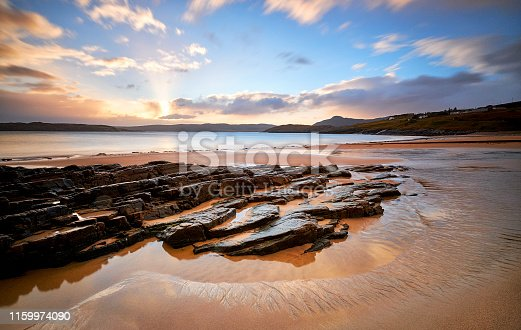 Wonderful beach in Talmine, Scotland. Rocks stick out of the sea. Beautiful sand in the foreground during a sunrise. This beach can be found while driving the north coast 500
