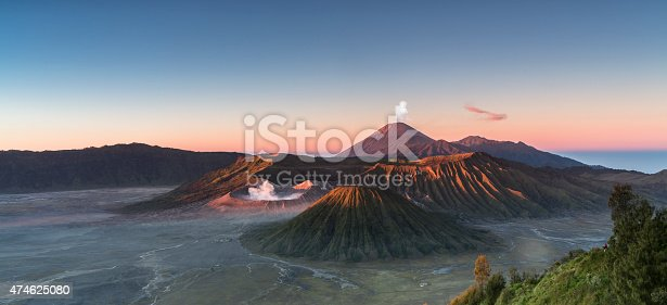 Early morning view of the Bromo caldeira in East Java in Indonesia. The volcanic formation of a few volcanoes, with the famous volcano Bromo and the Semeru volcano in the background attract everyday large crowds of visitors on the mountain top for sunrise.