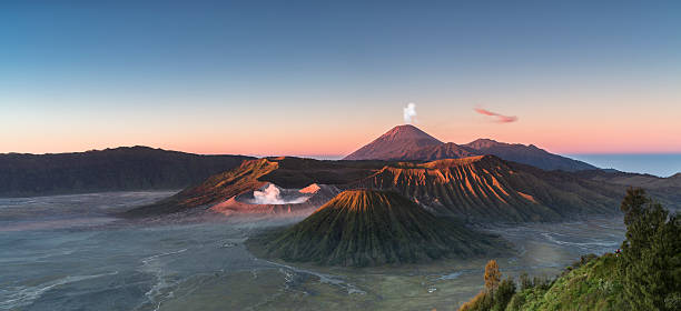 Sunrise at the Bromo volcano mountain in Indonesia Early morning view of the Bromo caldeira in East Java in Indonesia. The volcanic formation of a few volcanoes, with the famous volcano Bromo and the Semeru volcano in the background attract everyday large crowds of visitors on the mountain top for sunrise. volcanic landscape stock pictures, royalty-free photos & images