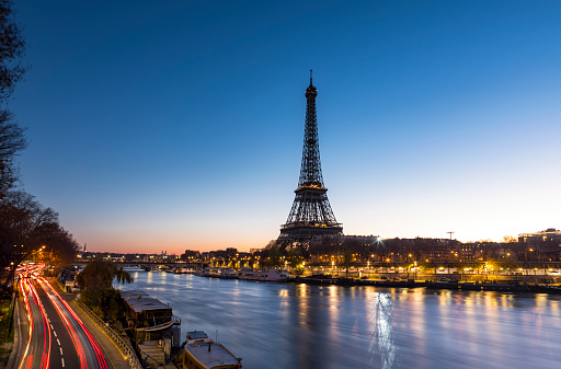 An early morning sunrise takes place behind the majestic Eiffel Tower in the city of Paris in France. Situated near the Seine river, the Eiffel Tower is one of the most important monument in the World. On the left side, cars are on the move and leave some trail lights.