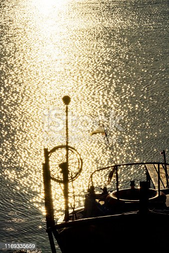 Golden hour glittering sunlight path with a boat at the fishermen's wharf in Ahtopol, Bulgarian Black Sea Coast