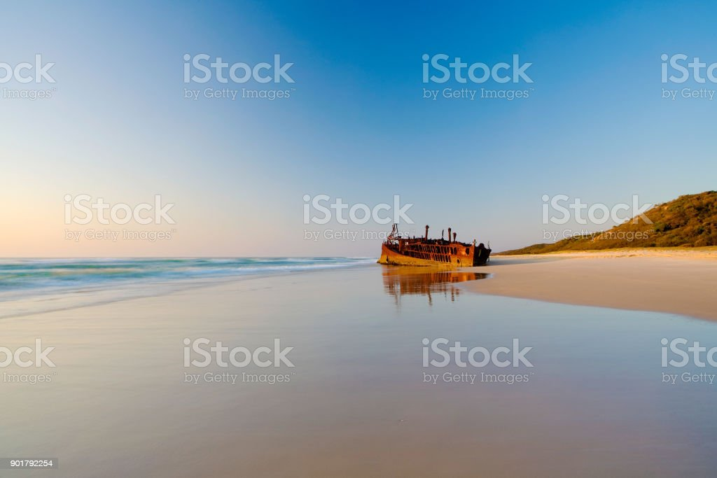 Sunrise at the Maheno Shipwreck on Fraser Island a vibrant sunrise at the Maheno Shipwreck on Fraser Island's 75 mile beach in Queensland, Australia Australia Stock Photo