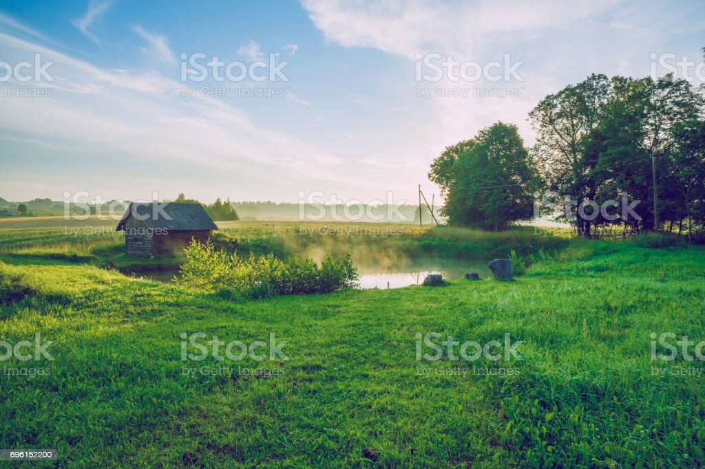 Sunrise at the pond with a view of the room and meadow. stock photo