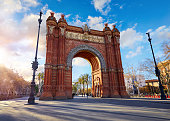 Sunrise at Triumphal Arch in Barcelona, Catalonia, Spain. Arc de Triomf at boulevard street. Alley with tropical palm trees. Early morning landscape with shadows and blue sky with clouds. Famous