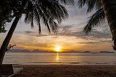 sunrise morning on sand beach \n between coconut tree, sun beam reflection on calm sea at Koh Yao Noi island, Thailand