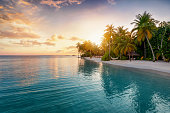 Sunrise behind a tropical island with palm trees, sandy beach and emerald sea in the Maldives