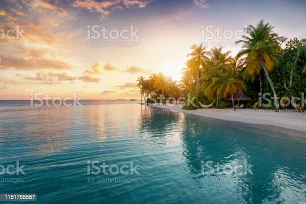 Photo of Sunrise behind a tropical island in the Maldives