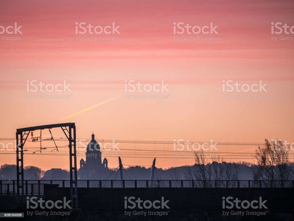 Sunrise behind Ashton Memorial Lancaster UK with Electric Rail cables in foreground stock photo