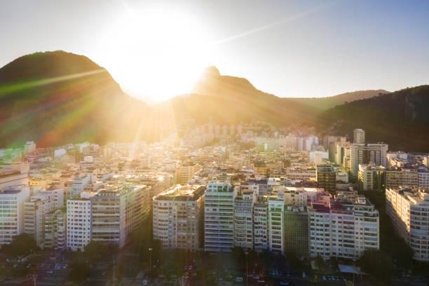 nascer do sol atrás dos montes em rio de janeiro, copacabana - sol nascente horizonte drone cidade - fotografias e filmes do acervo