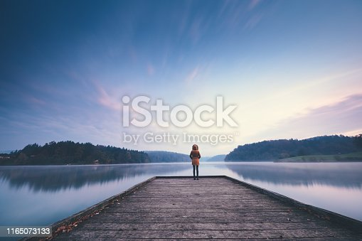 Woman standing on the jetty and watching colorful sunrise.
