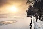 Woman walking by the frozen lake (Šmartinsko lake, Celje, Slovenia).