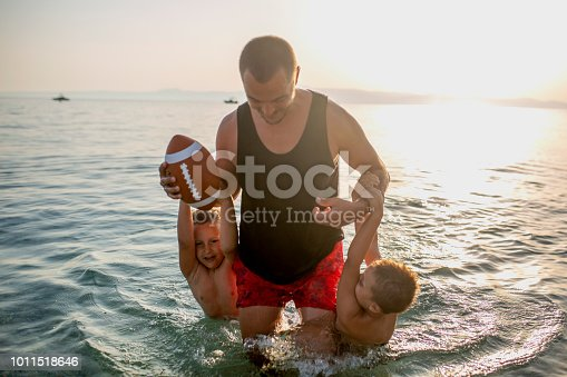 Father and his sons having fun at the beach