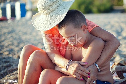 Grandmother with her grandsons having fun by the beach