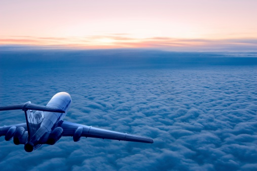 Passenger airplane on the clouds background. Flight in stratosphere. Daybreak.