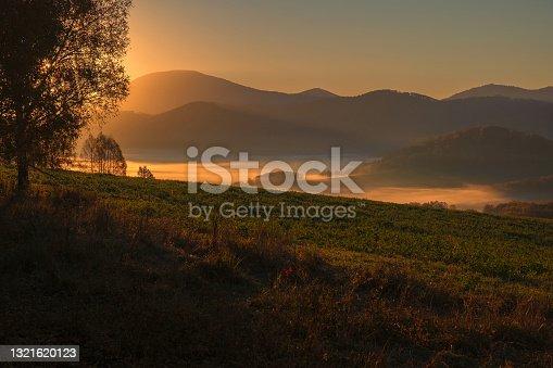 Sunrise, fog in a mountain valley. Autumn Altai.