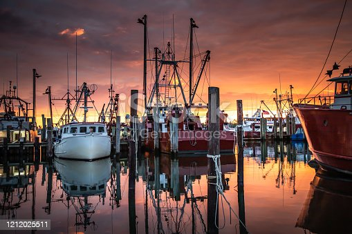 Wide shot of the fishing fleet at Viking Village while a wonderful sunrise unfolds in Barnegat Light, New Jersey