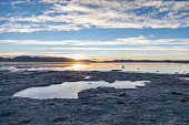 nice landscape in a frozen lake with a blue sky and the sun rising in the horizon